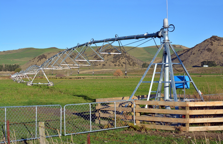 A pivot Irrigation Machine on a farm in North Canterbury, New Zealand ensures that fields are green and productive all year round. Stock Photo