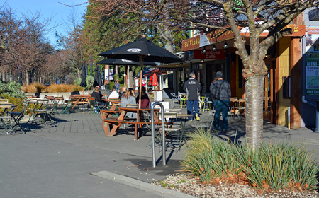 hot springs: Hanmer Springs, New Zealand - June 25, 2016: People at a popular outdoor cafe in the main street of the Tourist Town of Hanmer Springs, North Canterbury in winter.