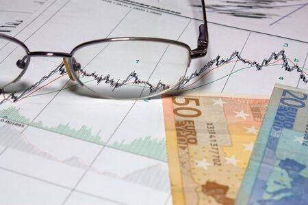 Glasses and Euro on graph of charts  photo