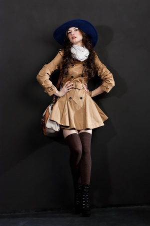 Expressive fashion studio shot of young and beautiful woman wearing brown overcoat on dark background. (Professional makeup and hair style). Stock Photo - 13090246