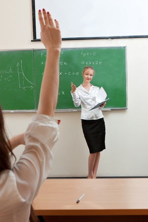 The teacher in the classroom on blackboard background  photo