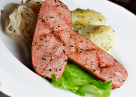 fried sausages in a white plate with lettuce. Stock Photo - 14369219