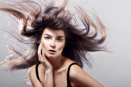 flying hair: fashion woman with flying hair on a gray background