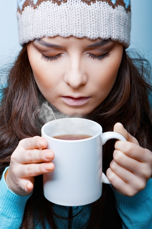 woman in a hat with hot tea closeup on a blue background photo