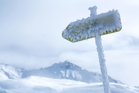 Frozen warning avalanche sign in Alps mountains, Tignes, France photo