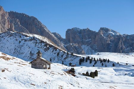 santas village: Old church in Dolomites Alps in winter on a sunny day, Italy