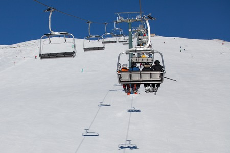 raiser: Skiers on the ski lift in Dolomiti Alps, Italy Stock Photo