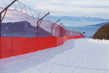 sella: Skiing slope bordered with red net, Dolomites, Italy Stock Photo