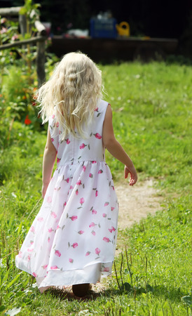 Little blond girl walking in the village photo