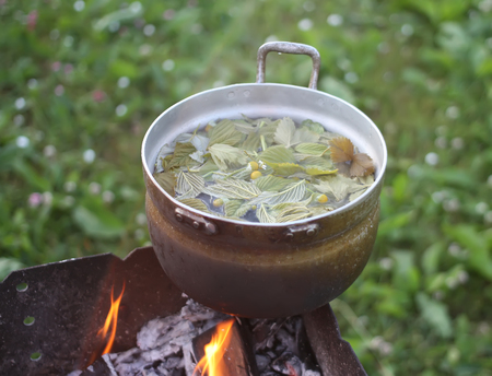 Old pan on stove outdoors in process of herbal tea preparation.