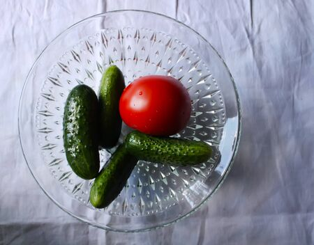 Fresh ripe cucumbers and tomato in a cup