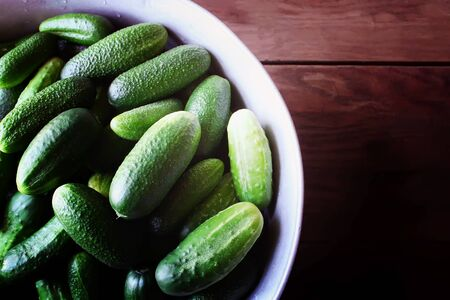 Fresh ripe cucumbers in a large cup on wooden background