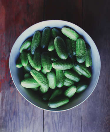 tendrils: Fresh ripe cucumbers in a large cup on wooden background
