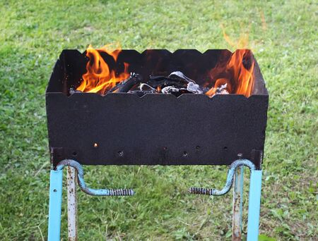 brazier: Bright flame of a burning fire above the brazier outdoors Stock Photo