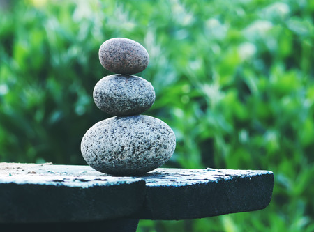 Pyramide of three oval stones on a wooden table outdoors