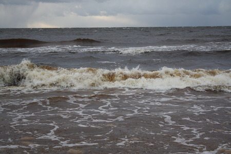 clear day in winter time: Sea water with small waves in Jurmala, Latvia. Coast of Baltic sea.
