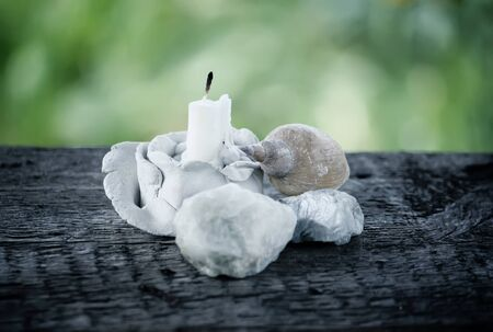 White candle in the decorative handmade clay candlestick with sea shells on wooden surface