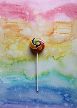 Sweet colorful lollipop on colorful decorative watercolor paper background.