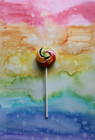 gum paste: Sweet colorful lollipop on colorful decorative watercolor paper background.