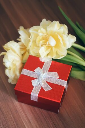 Yellow tulip flowers with red gift box on the table.