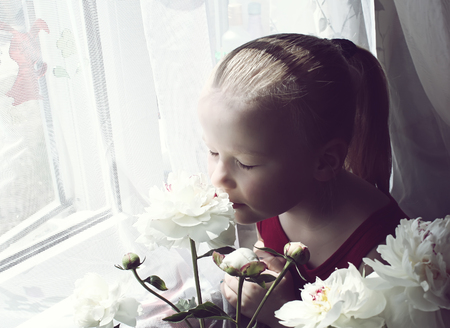 A little girl with peony flowers Stock Photo