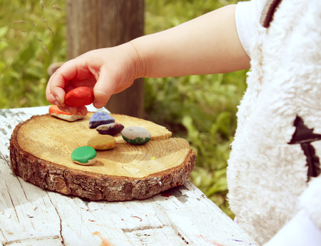 Childs hands with colored stones. Summer activity outdoors.