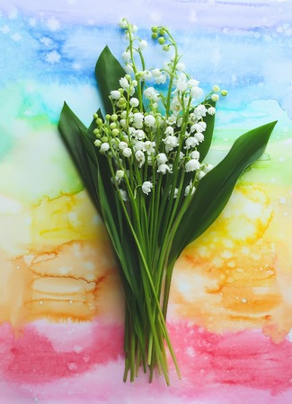 Lilies of the valley on a colorful watercolor background