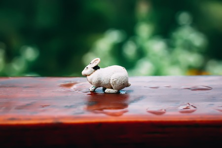 White small toy rabbit on a wooden surface outdoors.