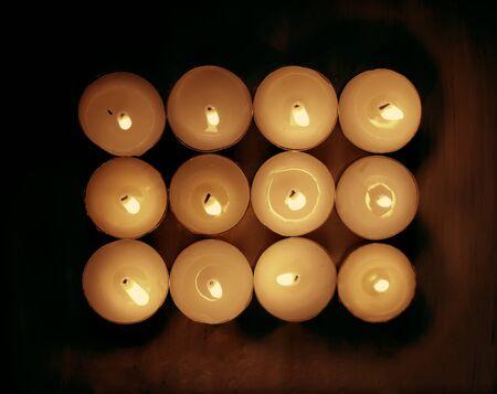12 burning candles on dark background.