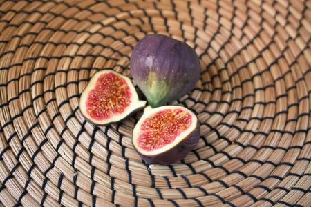 Fresh sweet ripe figs on wicker place mat background.rk background. Stock Photo