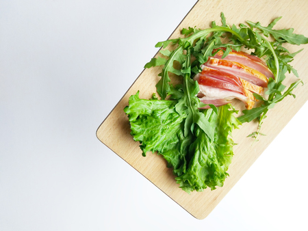 Sliced ham with fresh green lettuce and ruccola leaves on a cutting board.