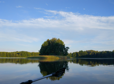 summer evening landscape with lake surface and fragment of paddle of inflatable boat. Latvia, East Europe.