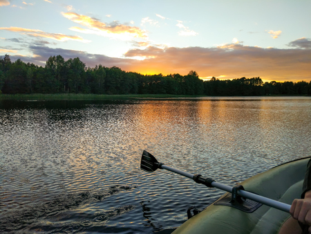 summer evening landscape with lake surface and fragment of paddle of inflatable boat. Sunset in Latvia, East Europe.
