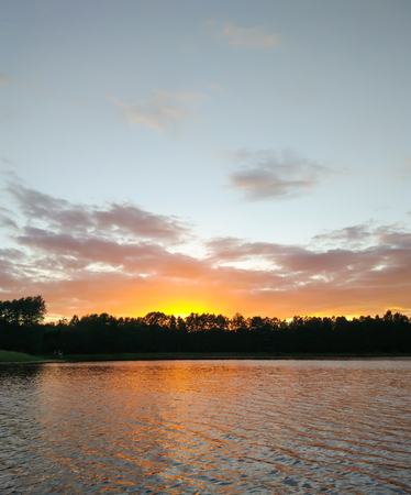 Calm lake surface at evening in Latvia, East Europe. summer sunset landscape with water and forest.