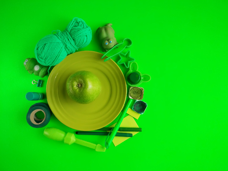 Set of different objects in green colors. Apple on ceramics plate, toy frogs, makers, tape, watercolor paints, lipstick, clip, tweezers, molds, acrylic yarn and stickers.