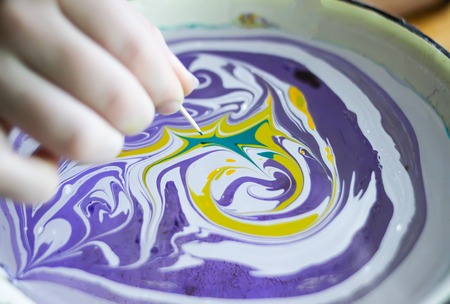 Process of creating ebru painting by colorful paints, paper and wooden stick. Bright abstract pattern in water.