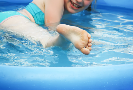 Little girl playing and spraying water in swimming pool outdoors at summer. Standard-Bild