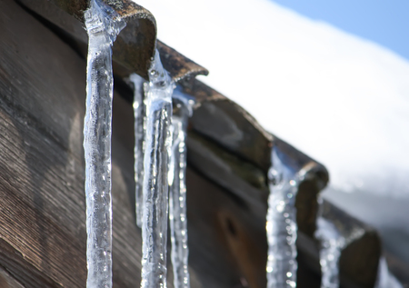 Shiny transparent icicles hanging on a roof close up. Stock Photo
