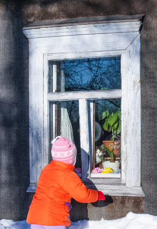 Little girl in an orange coat outdoors looking at cat on the window sill of country house in the village.