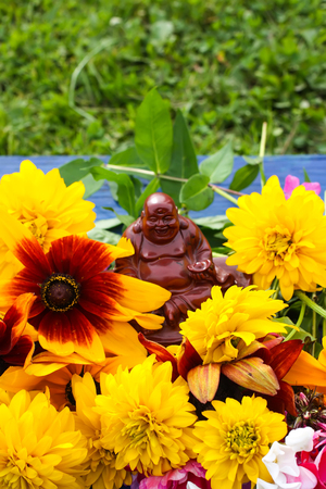 Bouquet of bright summer flowers and ceramic buddha figureine on colorful wooden boards.
