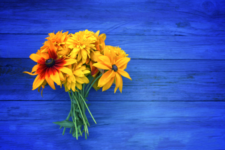Bouquet of bright summer rudbeckia flowers on blue wooden boards.