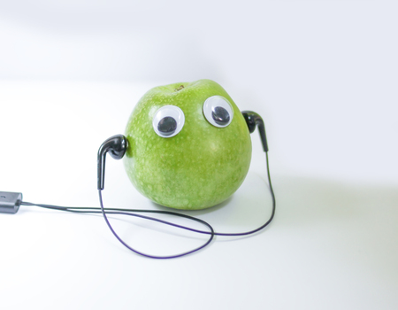 Green small apple with cute eyes and headphones on white background. Conceptual photo.