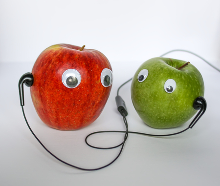 Red and green small apples with cute eyes and black headphones on white background. Conceptual photo. Reklamní fotografie