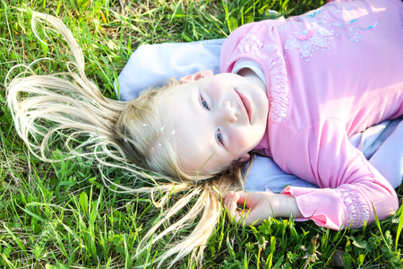 Cute little blonde girl with white petals of bird cherry tree on her hair lying on the green meadow in spring park.