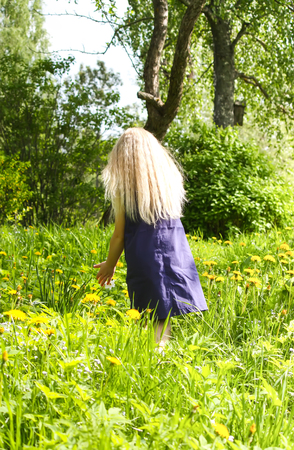 Cute little blonde girl on the meadow in summer park.