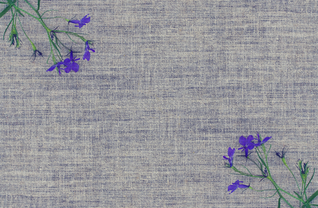 Natural linen texture with small bouquet of violet flowers. Natural fabric rough background. Imagens