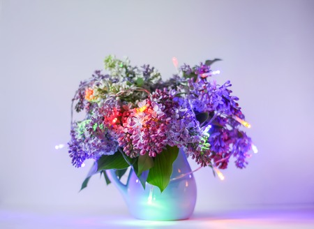Beautiful bouquet of fragrant purple flowers in blue ceramics vase on light background with festive garland colorful lights. Syringa vulgaris or lilacs plant. Stock Photo