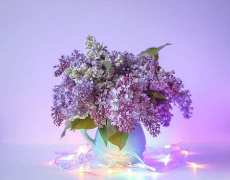 Beautiful bouquet of fragrant purple flowers in blue ceramics vase on light background with festive garland colorful lights. Syringa vulgaris or lilacs plant. Standard-Bild
