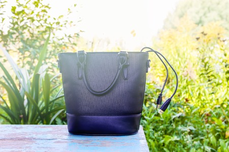 Black bag with usb cable on wooden bench outdoors.