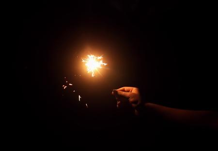 Female hand holding a burning sparkler on night darkness background. Stock Photo